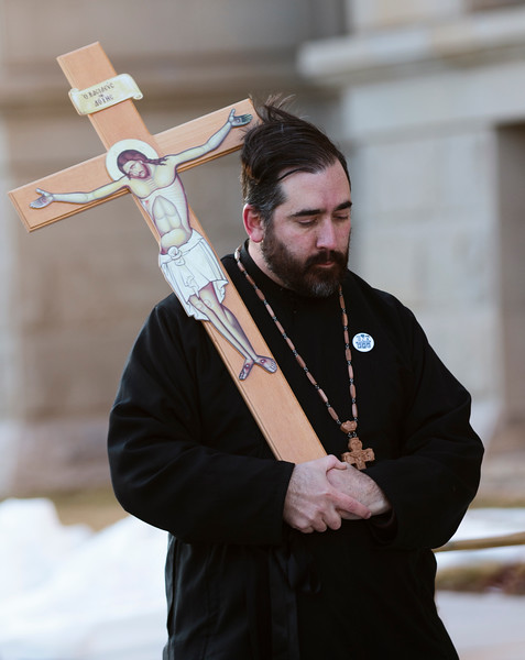 Father Christopher Xanthos of the Holy Apostles Orthodox Christian Church carries a crucifix on a march around the capitol in support of repealing the death penalty in Wyoming Monday, Dec. 9, 2019 in Cheyenne. Xanthos joined about twenty other marchers in a circuit of the capitol before marching down Capitol Street. Nadav Soroker/Wyoming Tribune Eagle