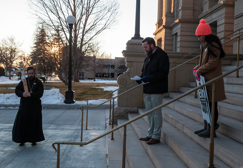 Father Christopher Xanthos of the Holy Apostles Orthodox Christian Church, left, and Kylie Taylor, the Wyoming coordinator of Conservatives Concerned about the Death Penalty, listen to Mike Leman, a deacon at Holy Trinity, say a prayer before a march around the capitol in support of repealing the death penalty in Wyoming Monday, Dec. 9, 2019 in Cheyenne. About twenty other marchers in a circuit of the capitol before marching down Capitol Street. Nadav Soroker/Wyoming Tribune Eagle