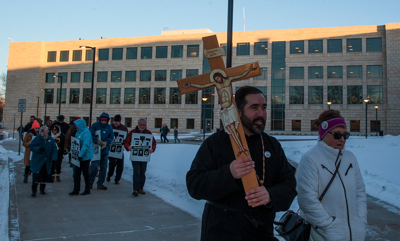 Father Christopher Xanthos of the Holy Apostles Orthodox Christian Church carries a crucifix with Holly Garrard on a march around the capitol in support of repealing the death penalty in Wyoming Monday, Dec. 9, 2019 in Cheyenne. Xanthos joined about twenty other marchers in a circuit of the capitol before marching down Capitol Street. Nadav Soroker/Wyoming Tribune Eagle