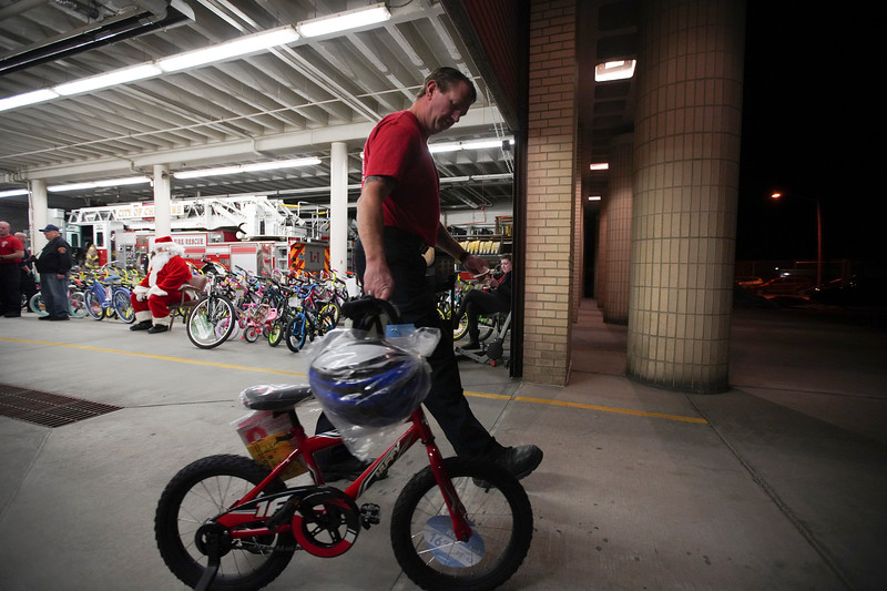 Cheyenne firefighter Eric Bickell walks a bike out for a family during the third annual bike drive Friday, Dec. 20, 2019 at Cheyenne Fire Rescue Station 1. The firefighters collected about 100 bikes to give away to kids. Nadav Soroker/Wyoming Tribune Eagle
