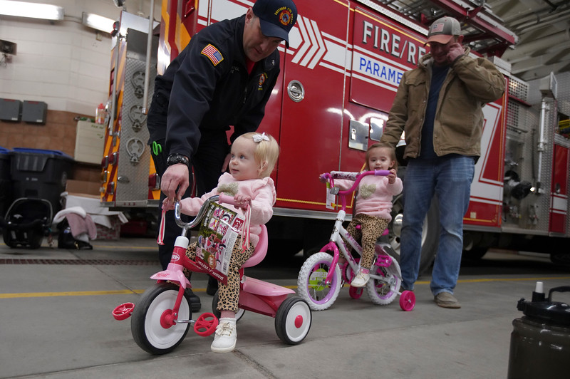 Cheyenne Fire Rescue paramedic Dave Beightol helps Finley Coonts, 1, with her new bike as Johnny Coonts helps Josie Coonts, 1, at the Local 279 Firefighters' third annual bike drive Friday, Dec. 20, 2019 at Cheyenne Fire Rescue Station 1. The firefighters collected about 100 bikes to give away to kids. Nadav Soroker/Wyoming Tribune Eagle