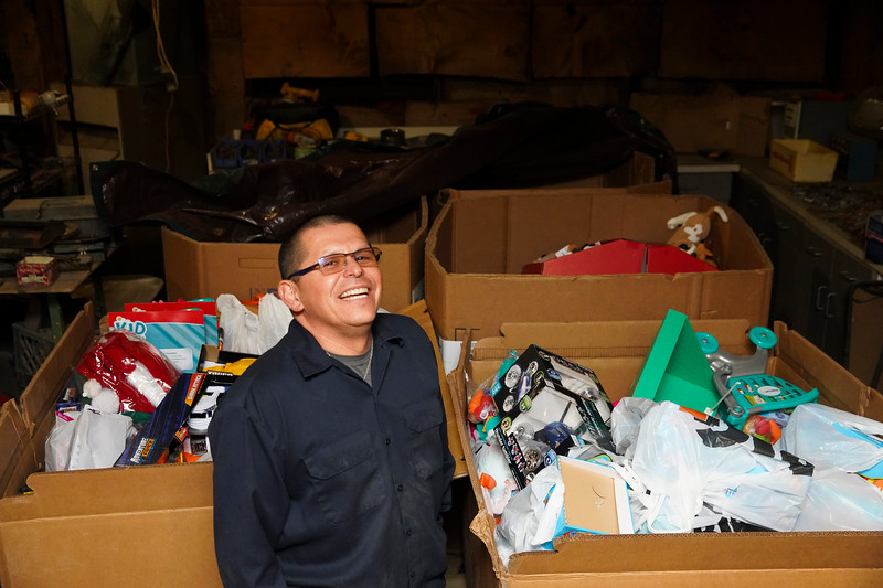 Ruben Castaneda stands for a portrait in front of the four large bins of toys he has raised to give away to kids for Christmas Monday, Dec. 23, 2019 at Ruben's Metals. Castaneda is continuing a tradition that his father, also Ruben, started. Nadav Soroker/Wyoming Tribune Eagle