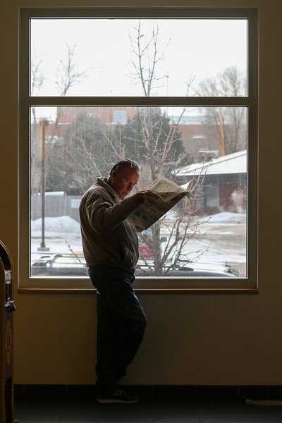 Vince Osborn reads Traders in the lobby while waiting for the library to open Friday, Dec. 27, 2019 at the Laramie County Library in Cheyenne. Osborn, there to check out some books, was part of a crowd of people waiting for the gate to lift at 10 a.m. Nadav Soroker/Wyoming Tribune Eagle