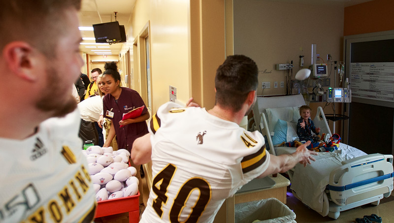 Wyoming kicker Cooper Rothe throws a ball to Justin, 4, Sunday, Dec. 29, 2019 at the Diamond Childrens Hospital in Tucson. Members of the Wyoming Cowboys and Georgia State Panthers visited children at the hospital before their game in the Arizona Bowl. Nadav Soroker/Wyoming Tribune Eagle
