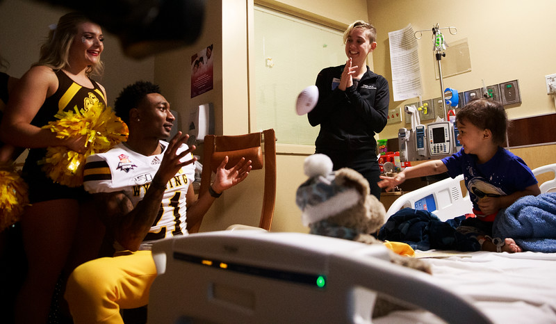 Santiago, 3, right, throws Wyoming corner back C.J. Coldon the ball as they play pass in his room Sunday, Dec. 29, 2019 at the Diamond Childrens Hospital in Tucson. Members of the Wyoming Cowboys and Georgia State Panthers visited children at the hospital before their game in the Arizona Bowl. Nadav Soroker/Wyoming Tribune Eagle