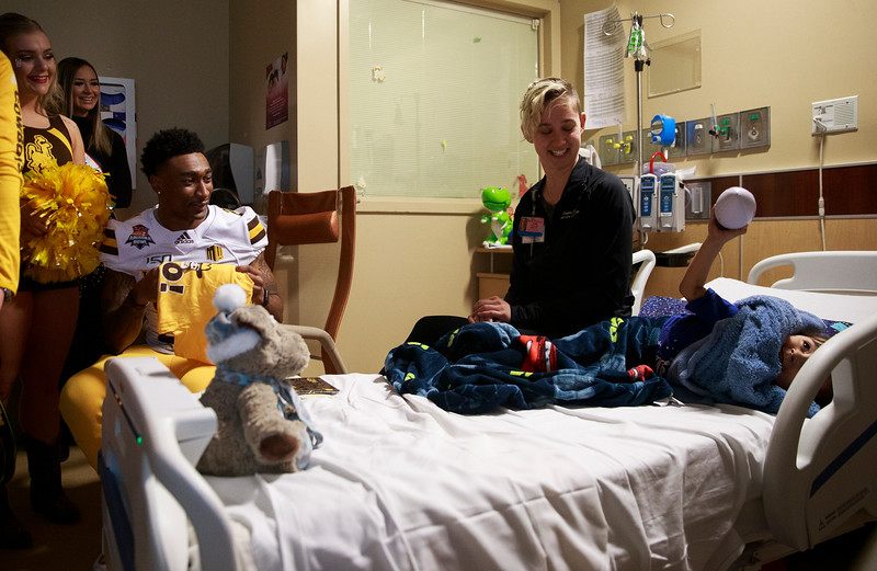 Santiago, 3, right, holds up a ball as members of the Wyoming Cowboys and cheer team visit him in his room Sunday, Dec. 29, 2019 at the Diamond Childrens Hospital in Tucson. Members of the Wyoming Cowboys and Georgia State Panthers visited children at the hospital before their game in the Arizona Bowl. Nadav Soroker/Wyoming Tribune Eagle
