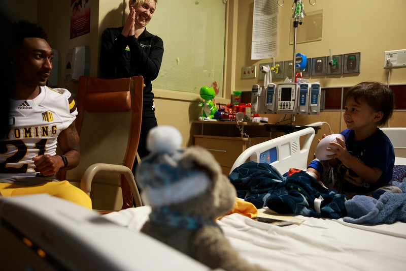 Santiago, 3, right, catches a ball from Wyoming corner back C.J. Coldon as they play pass in his room Sunday, Dec. 29, 2019 at the Diamond Childrens Hospital in Tucson. Members of the Wyoming Cowboys and Georgia State Panthers visited children at the hospital before their game in the Arizona Bowl. Nadav Soroker/Wyoming Tribune Eagle