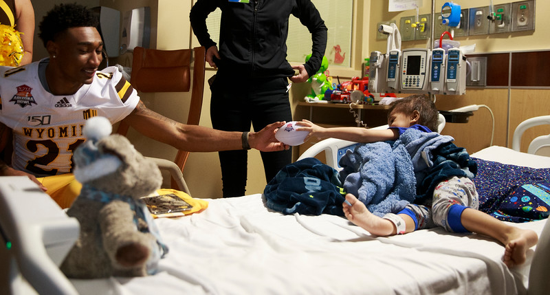 Santiago, 3, right, hands Wyoming corner back C.J. Coldon the ball as they play pass in his room Sunday, Dec. 29, 2019 at the Diamond Childrens Hospital in Tucson. Members of the Wyoming Cowboys and Georgia State Panthers visited children at the hospital before their game in the Arizona Bowl. Nadav Soroker/Wyoming Tribune Eagle