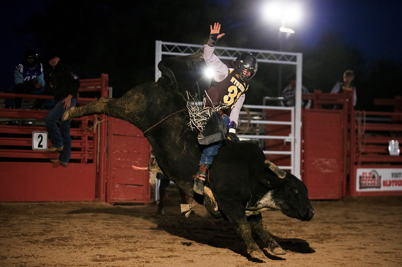 A cowboy wearing a Wyoming Cowboys jersey rides a bull Sunday, Dec. 29, 2019 at Old Tucson in Tucson. Old Tucson, a movie studio and theme park hosts teams for rodeo, dinner and a show before the Arizona bowl. Nadav Soroker/Wyoming Tribune Eagle