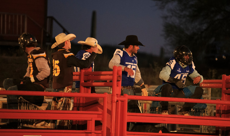 Cowboys wearing Wyoming Cowboys and Georgia State Panthers football jerseys sit on the rails before the start of a rodeo for Wyoming and Georgia State Sunday, Dec. 29, 2019 at Old Tucson in Tucson. Old Tucson, a movie studio and theme park hosts teams before the Arizona bowl. Nadav Soroker/Wyoming Tribune Eagle