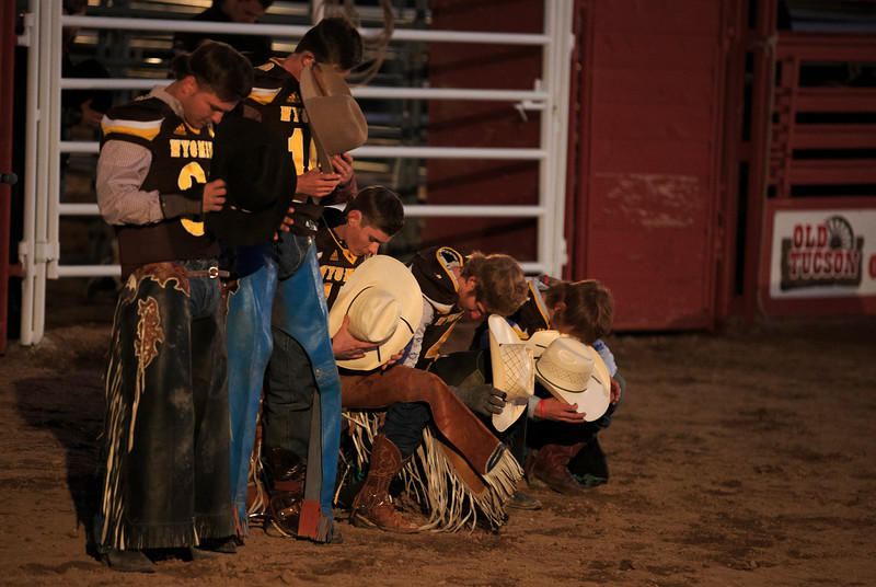 Cowboys wearing Wyoming Cowboys football jerseys pray before the start of a rodeo for Wyoming and Georgia State Sunday, Dec. 29, 2019 at Old Tucson in Tucson. Old Tucson, a movie studio and theme park hosts teams before the Arizona bowl. Nadav Soroker/Wyoming Tribune Eagle
