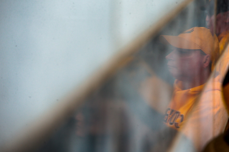 Ed Telgenhoff is reflected in the marble of a building as he watches the pep rally Monday, Dec. 30, 2019 in downtown Tucson. University of Wyoming Cowboys fans joined the Western Thunder Marching band and spirit squad in a pep rally against the Georgia State University Panthers fans and band. Nadav Soroker/Wyoming Tribune Eagle
