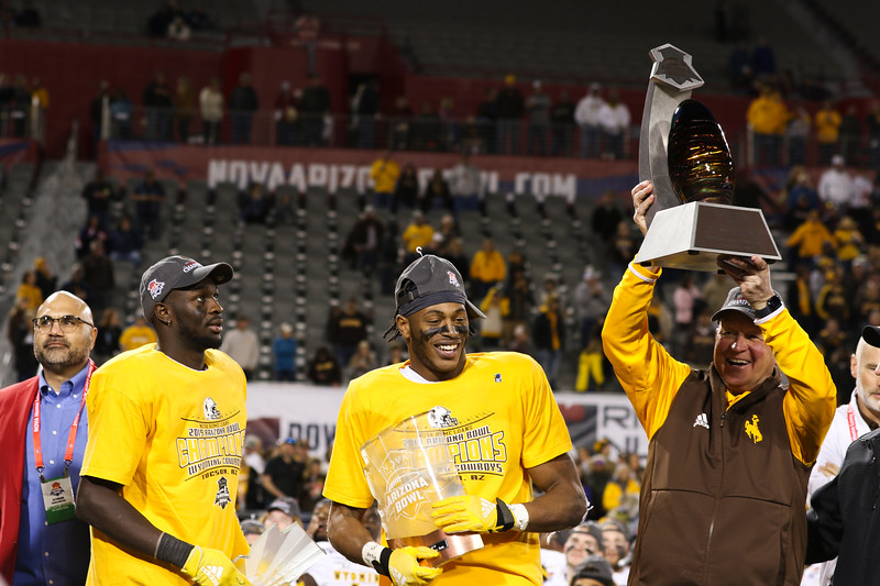 Wyoming head coach Craig Bohl, right, holds up the Arizona Bowl trophy with defensive MVP Alijah Halliburton (3) and offensive MVP Xazavian Valladay (6) on the victors' stage Tuesday, Dec. 31, 2019 at the University of Arizona. The Wyoming Cowboys defeat the Georgia State Panthers 38-17 to win the Arizona Bowl. Nadav Soroker/Wyoming Tribune Eagle