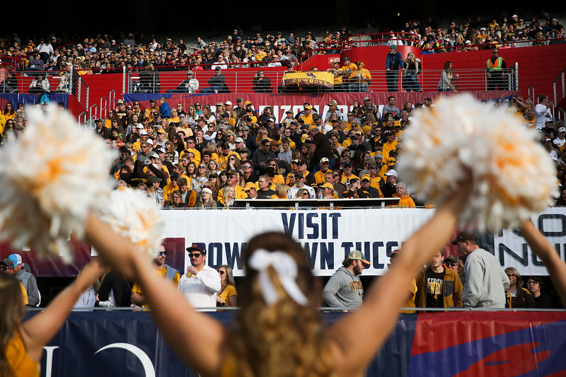 Wyoming fans are framed by a Wyoming cheerleader's pompoms Tuesday, Dec. 31, 2019 at the University of Arizona. The Wyoming Cowboys lead the Georgia State Panthers 24-10 at halftime in the Arizona Bowl. Nadav Soroker/Wyoming Tribune Eagle