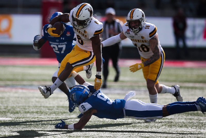 Wyoming running back Xazavian Valladay (6) attempts to leap over Georgia State safety Cedric Stone (9) Tuesday, Dec. 31, 2019 at the University of Arizona. The Wyoming Cowboys lead the Georgia State Panthers 24-10 at halftime in the Arizona Bowl. Nadav Soroker/Wyoming Tribune Eagle