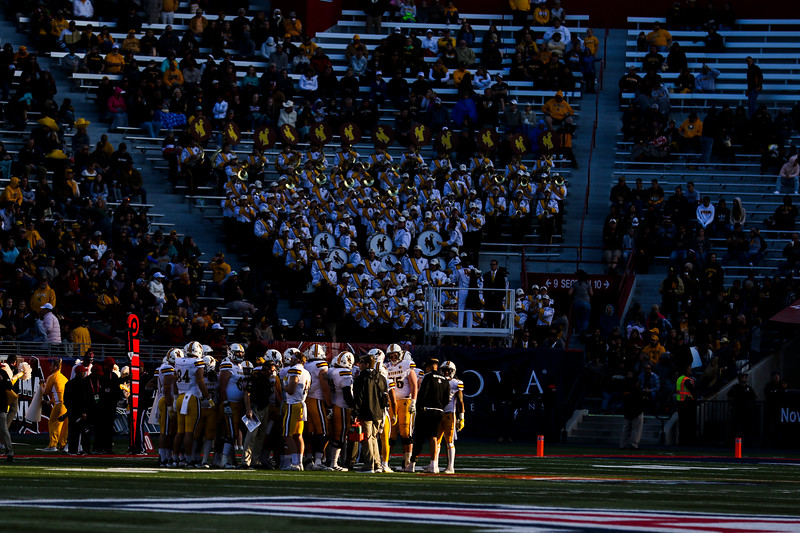 The Cowboys huddle in a slice of light Tuesday, Dec. 31, 2019 at the University of Arizona. The Wyoming Cowboys defeat the Georgia State Panthers 38-17 to win the Arizona Bowl. Nadav Soroker/Wyoming Tribune Eagle