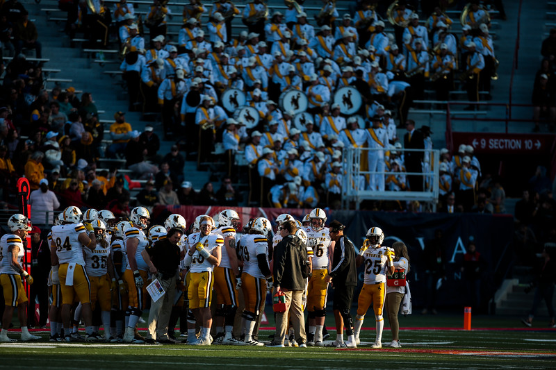 The Cowboys huddle in a slice of light during the third quarter Tuesday, Dec. 31, 2019 at the University of Arizona. The Wyoming Cowboys defeat the Georgia State Panthers 38-17 to win the Arizona Bowl. Nadav Soroker/Wyoming Tribune Eagle