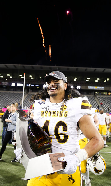 Wyoming linebacker Cassh Maluia (46) runs with the Arizona Bowl trophy as fireworks explode over the north stands Tuesday, Dec. 31, 2019 at the University of Arizona. The Wyoming Cowboys defeat the Georgia State Panthers 38-17 to win the Arizona Bowl. Nadav Soroker/Wyoming Tribune Eagle