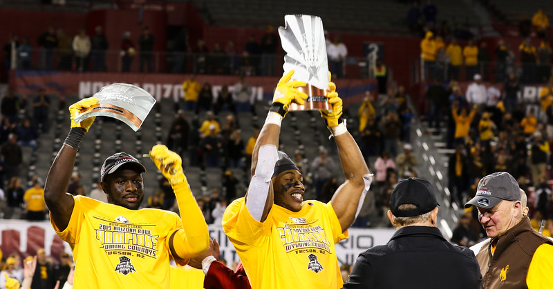 Arizona Bowl defensive MVP Alijah Halliburton (3) and offensive MVP Xazavian Valladay (6) hoist their trophies on the stage after the Cowboys' victory Tuesday, Dec. 31, 2019 at the University of Arizona. The Wyoming Cowboys defeat the Georgia State Panthers 38-17 to win the Arizona Bowl. Nadav Soroker/Wyoming Tribune Eagle