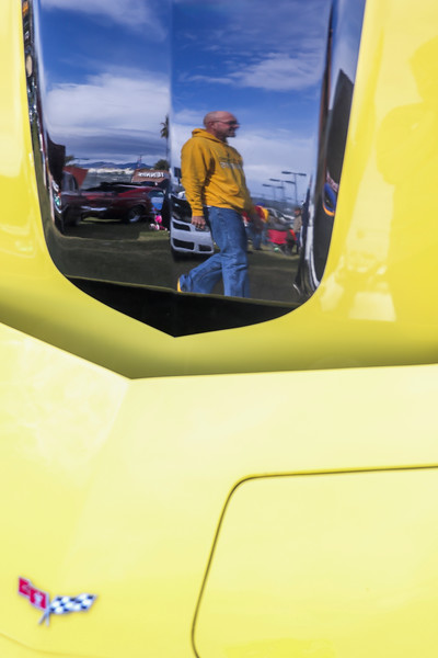 Greg Leitz is reflected in the hood of a yellow corvette as he walks past in the car show area of the tailgate Tuesday, Dec. 31, 2019 at the University of Arizona. Wyoming Fans fill the Arizona Bowl tailgate area before the Cowboys take on the Georgia State University Panthers. Nadav Soroker/Wyoming Tribune Eagle
