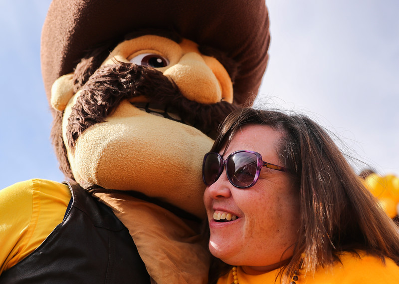 Karen Anderson hugs Pistol Pete in the tailgate area Tuesday, Dec. 31, 2019 at the University of Arizona. Wyoming Fans fill the Arizona Bowl tailgate area before the Cowboys take on the Georgia State University Panthers. Nadav Soroker/Wyoming Tribune Eagle