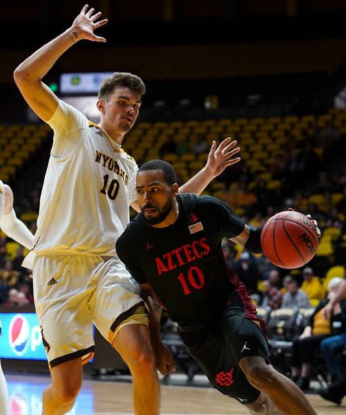 San Diego State guard KJ Feagin (10) attempts to drive past Wyoming forward Hunter Thompson (10) to get under the basket Wednesday, Jan. 8, 2020 in Arena-auditorium. The University of Wyoming basketball team loses to San Diego State 72-52. Nadav Soroker/Laramie Boomerang