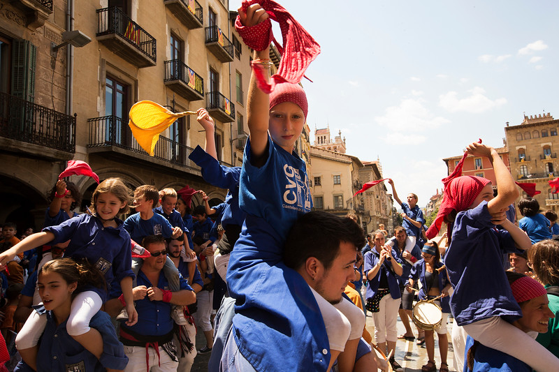 Young castellars dance around on the shoulders of their older relatives after the end of the tower building in Vic, Catalonia on the last day of a festival.