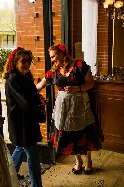 Abigail Chambers, one of the Tudor Rose's singing waitstaff, lets in the first official patron of the Tudor Rose English Tea Room at 11 a.m. Saturday Morning.