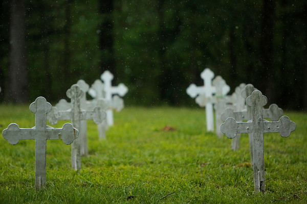 Graves rest under a misting of rain. The graveyard, behind the abbey, hosts monks and other members of the monastery community.