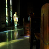 Father Cyprian walks into the church at Assumption Abbey as evening light streams in through stained glass windows.