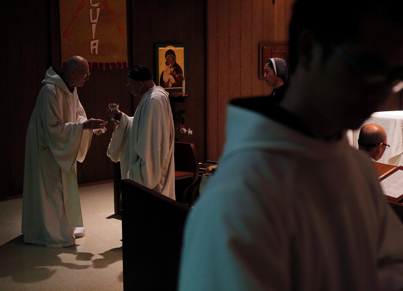 Father Cyprian gives communion to Brother Thomas during morning mass. Because more than half of the monks are ordained, they take turns offering communion to their fellows and visiting guests.