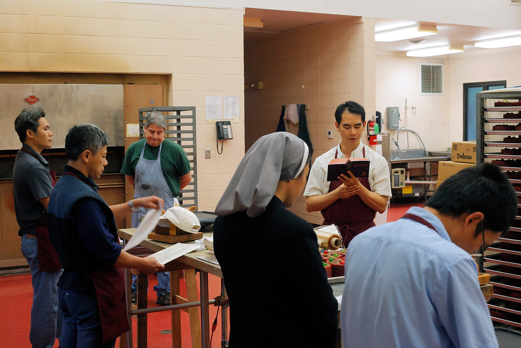 Brother Alphonse leads a prayer over the Abbey's fruitcake decorating table. As part of their religious duty Trappist monks are expected to work to provide for themselves, many monasteries producing products from beer to caskets.