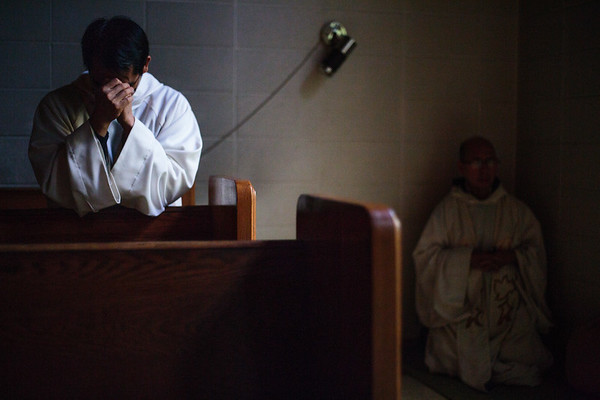 Brother Alphonse prays in a pew while the Abbey's Superior, Father Alberic, prays on a mat behind him. Father Alberic is a Trappist Monk and Brother Alphonse is a Cistercian, the two orders coming together at Assumption Abbey after the founding Trappists grew too old to accept novices.