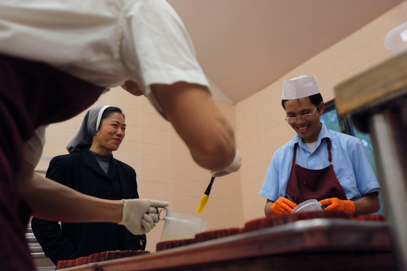 "Sister Faustina, a visiting nun from Springfield, Missouri, laughs with Brother Gabriel as he and Brother Alphonse decorate fruitcakes. Before making fruitcakes, the monks at Assumption Abbey made cinderblocks. When they changed products they had a joking slogan, ""If you liked our concrete blocks, you'll love our fruitcake."""