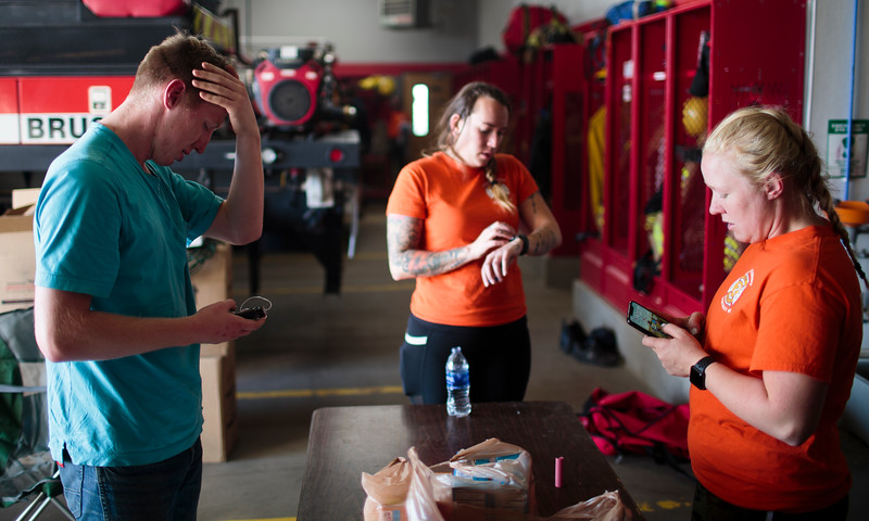 Albert Byrd, left, checks his insulin pump while Amanda Brooks and Mickey Sanderson check messages after a round with live fire Saturday, Oct. 19, 2019 at the Laramie County Fire District 2 practice grounds. Nadav Soroker/Wyoming Tribune Eagle