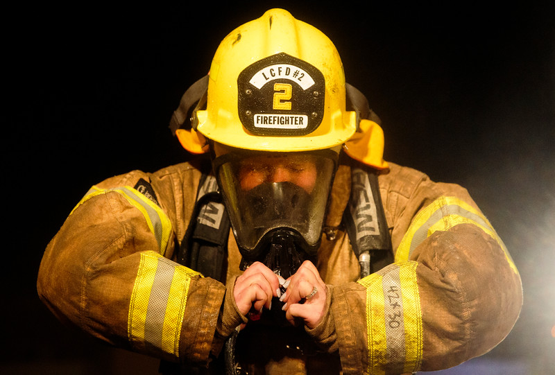 Mickey Sanderson pulls off her regulator after practicing a transitional fire attack during the Laramie County Fire District 2 volunteer fire academy, Wednesday, October 9, 2019 at Fire Station 1. The regulator is part of the Self-Contained Breathing Apparatus and is the first thing to come off once the trainees exit the structure. Nadav Soroker/Wyoming Tribune Eagle