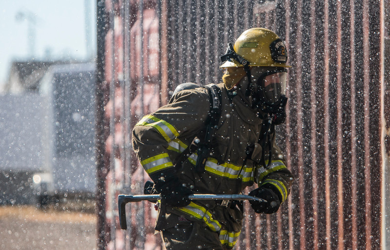 Albert Byrd carries the halligan tool through a shower of water sprayed by Yevgeniy Sokolov during they rlive live fire practice Saturday, Oct. 19, 2019 at the Laramie County Fire District 2 practice grounds. The live fire training was an opportunity to put all their practice in previous weeks to use. Nadav Soroker/Wyoming Tribune Eagle