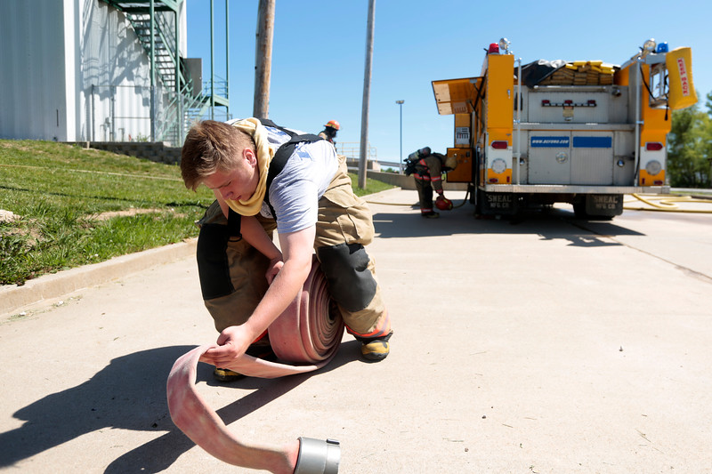 Wyatt Dawdy wraps up a hose after training on June 8 at the Fire District's training area. After hours of hauling hose and fighting practice fires the recruits are still responsible for helping pack everything up.