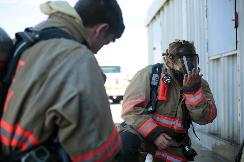 Wyatt Dawdy activates his SCBA mask during a dry run of a transitional fire attack on June 8 at the Fire District's training facility. In a transitional attack the fire fighters start by attacking the fire from outside before moving into the building to finish extinguishing it.