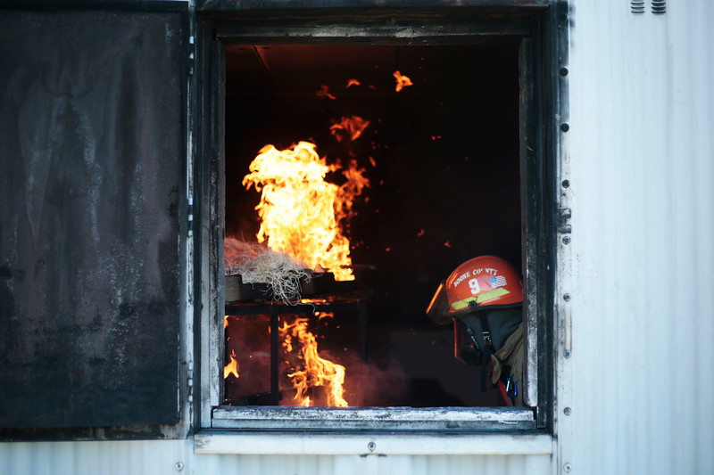 A fire instructor ignites wood pallets and straw for a transitional fire attack drill on June 8 at the Fire District's training area in Columbia, Missouri. Trainees went through multiple repetitions of the drill in athletic wear and then in full bunker gear to build muscle memory and learn what to do before dealing with live fire.