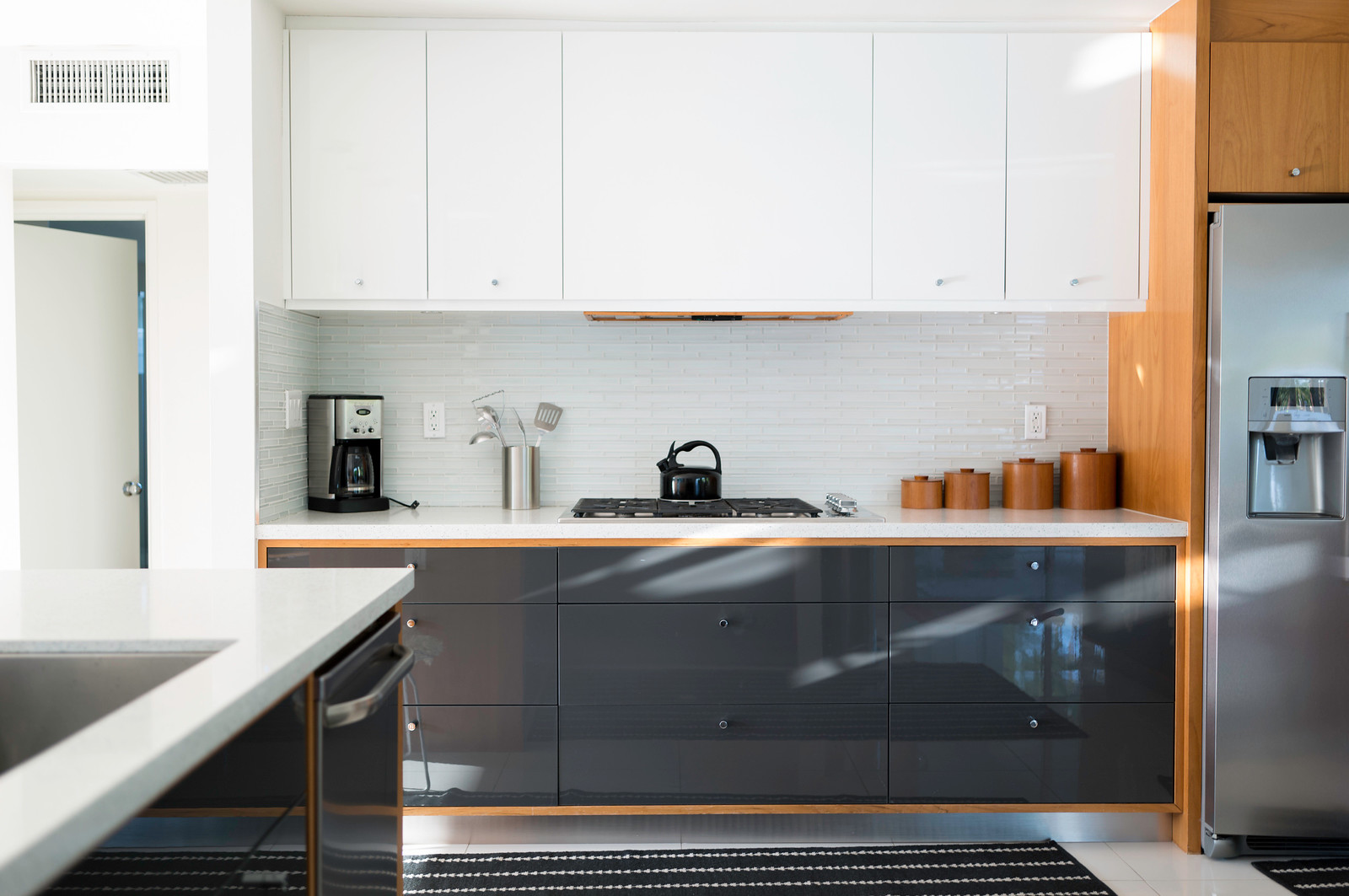 White kitchen cabinets above stove with black kitchen cabinets below