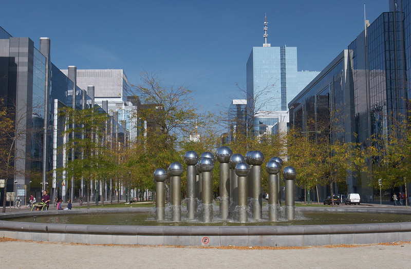 La Fontaine par Pol Bury (1995)  21 colonnes de 2 à 3 m en acier inoxydable, avec des têtes sphériques qui à l'origine étaient mobiles sous l'effet de l'eau qui ruisselle. Le mouvement lent de cette sculpture cinétique devait contraster avec le monde trépidant des affaires de l'Espace Nord.  Hélas l'artiste n'avait pas songé au vent qui, quand il était fort, jetait les sphères dans le bassin. C'est la raison pour laquelle beacoup de ces sphères ont maintenant été clouées et sont devenues immobiles.