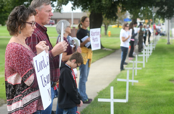 Jo Bierman of Effingham prays the Rosary along Fayette Avenue in Effingham during National Respect Life and Life Chain Sunday afternoon. At her side is her husband, Mike. They have two adopted children and have been participating in the event since its inception.