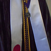 Representing 4 years of effort: White stole represents the Japanese Flag for her exchange to Japan, the purple and yellow cords are her fraternity colors, the yellow cords are for achieving honors with a GPA above 3.4, the medallion is for her selection as a McNair scholar and the three pins are for the three years she served as an orientation assistant.
