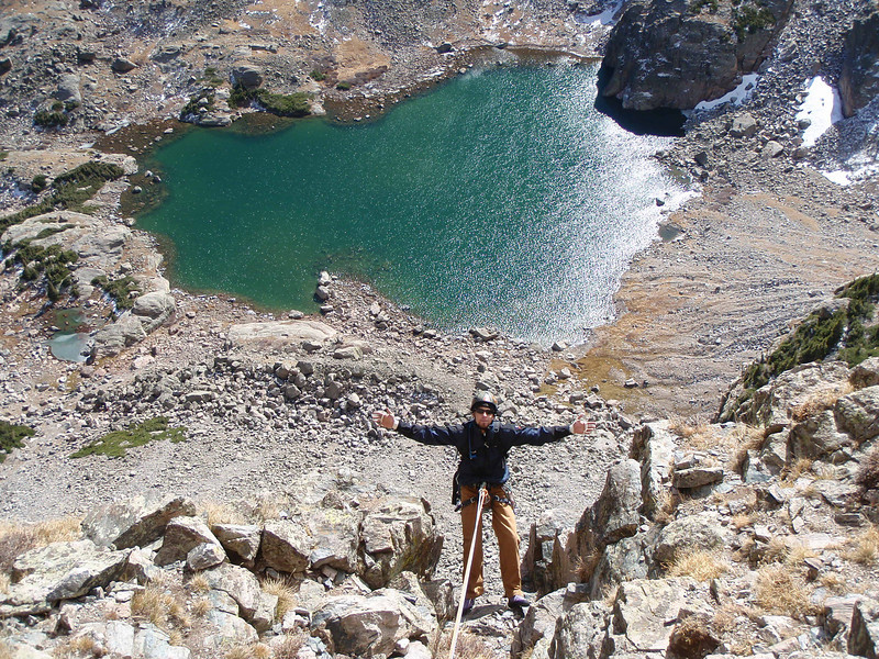 Daniel appears over the lip of the terrace with Sky Pond below. Sky Pond is at 10,893' and Petit tops out at 12,000'.