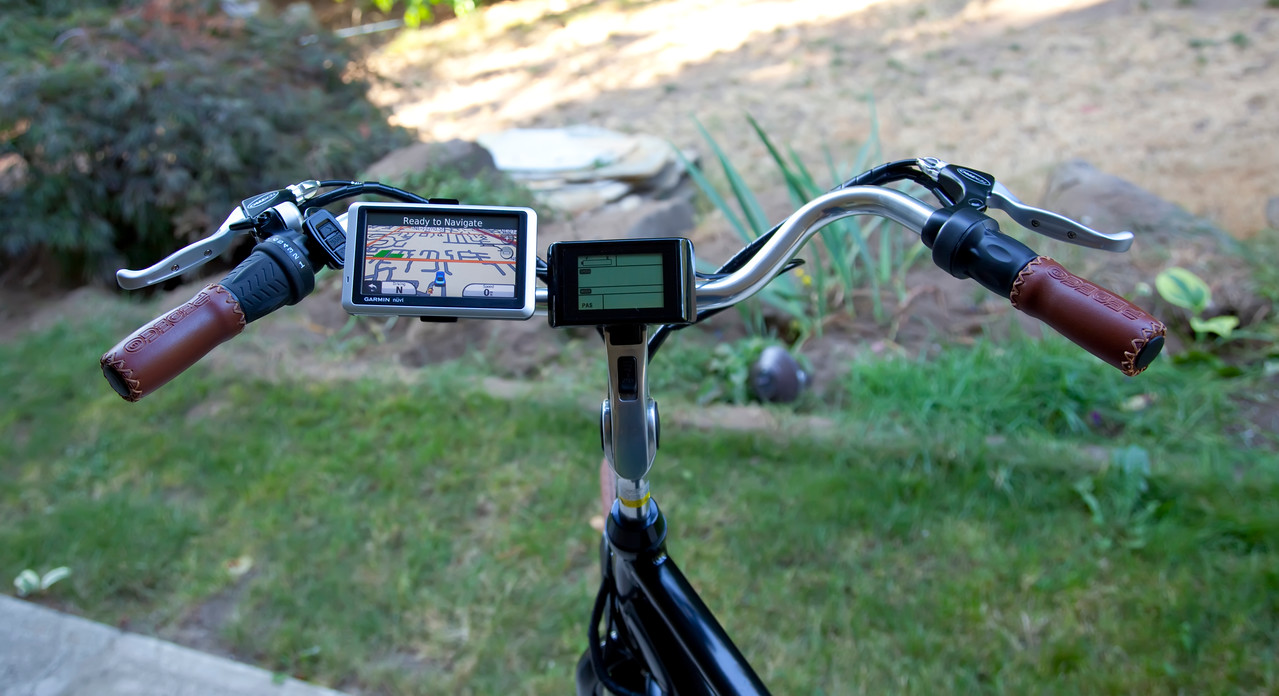My Pedego Classic City Commuter drivers dashboard. Built in computer for things like battery life, mph, power modes, etc. Various fingertip controls for changing gears, power settings, throttle, etc. Then, of course, I have also added the Garmin Nuvi GPS. I have been using a small mirror mounted to my helmet. I have decided to add a larger handlebar mirror. So when that gets mounted it will be in this view as well.