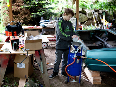 Since we've never used a media (sand) blaster before, we did online research and decided that the right thing to do was use aluminum oxide media. Here you can see Nate screening the media as he loads the blaster. It didn't take very much of this to figure out that it just wasn't getting the job done, so we went to Home Depot and got sand. Now things started working.