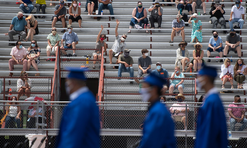 Guests wave to the graduates as they file in during the processional during the Poudre High School graduation ceremony at French Field at Rocky Mountain High School Saturday, July 25, 2020. Poudre School District's graduation ceremonies were delayed and adapted to accommodate social distancing and other precautions aimed at limiting the spread of COVID-19.