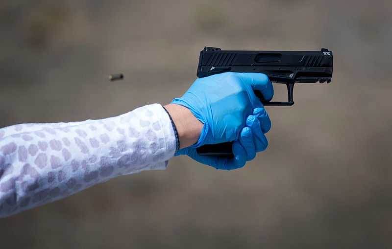 A woman, who has asthma, wears protective gloves as she fires a semi-automatic handgun during a firearms safety course conducted by Joseph Wilkey of Level Up Firearms amid the coronavirus pandemic outside Loveland, Colo. on Tuesday, March 24, 2020.