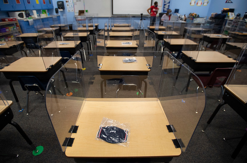 A mask lies on a desk surrounded by plastic shielding at Liberty Common Elementary School in Fort Collins, Colo. on Friday, Aug. 21, 2020. While both Poudre and Thompson School Districts are starting classes remotely, some charter and private schools are resuming in-person learning.